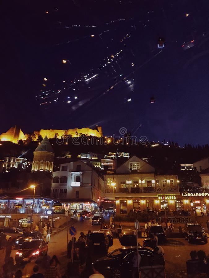 Night streets of Tbilisi. Bus travelling in the streets of Night summer Tbilisi. Cars and busses are rushing by. City is filled with light. Beautiful buildings royalty free stock image