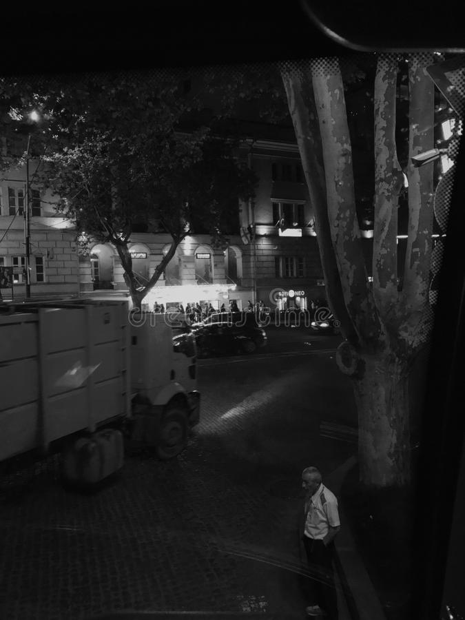 Night streets of Tbilisi in monochrome. Black and white photo of male figure standing against the road with truck rushing by. Photo is shot from above stock images