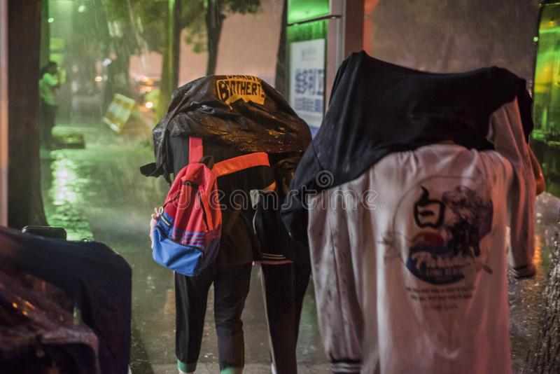 At night, a sudden downpour, three middle school students used their tops to block their heads and walked in the rain. stock photography