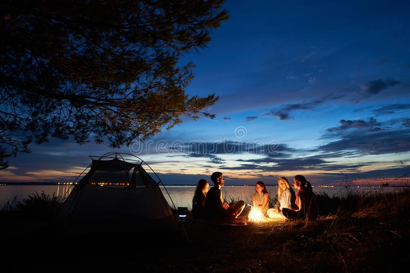 Night summer camping on shore. Group of young tourists around campfire near tent under evening sky royalty free stock photo
