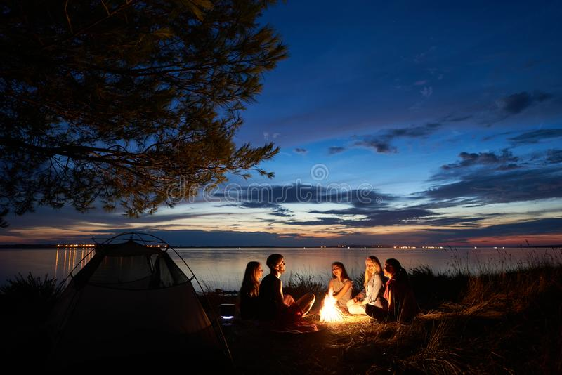 Night summer camping on shore. Group of young tourists around campfire near tent under evening sky stock images