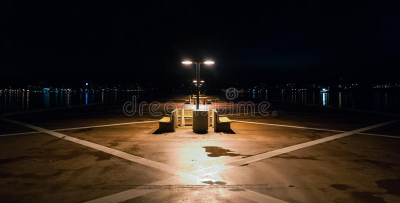 Night time on a lonely pier in Halifax, Nova Scotia. Halifax city lights across the harbor. royalty free stock image