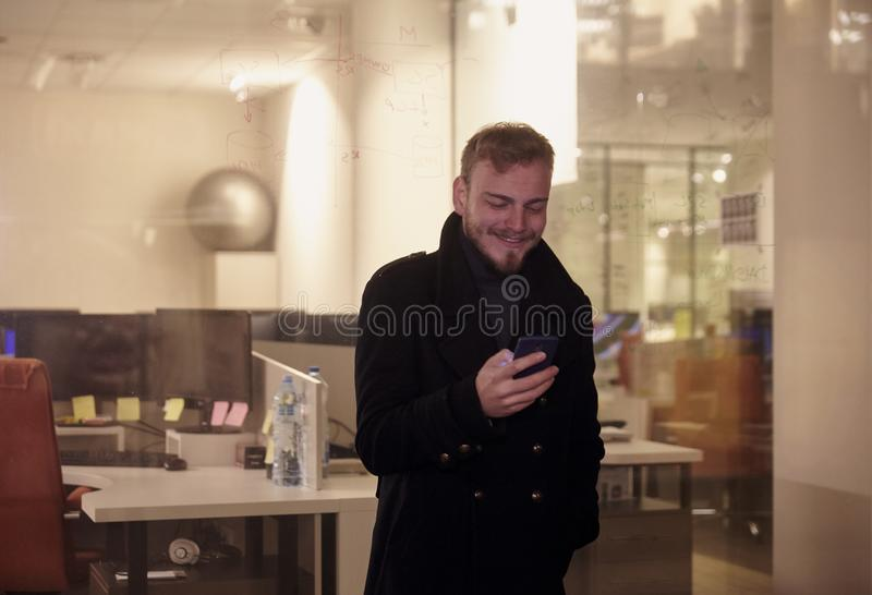 Night time, one young man, 20-29 years, looking at this looking at his smartphone, standing in Autumn coat in front of business stock photography