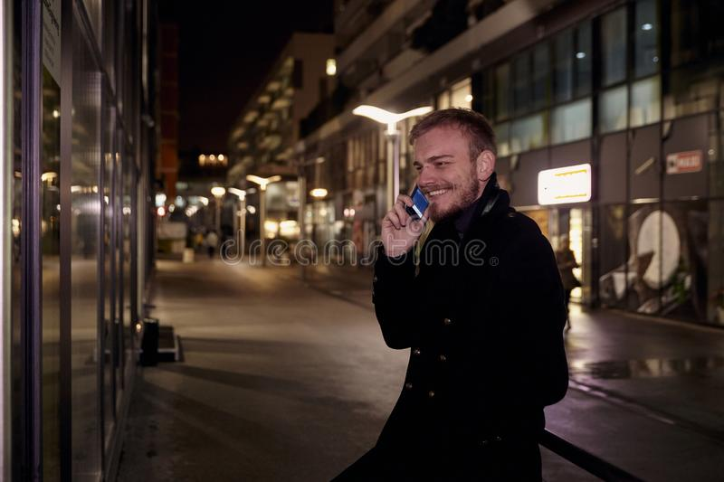 Night time, one young smiling and happy man, 20-29 years, talking over his phone, standing in Autumn coat on street, in business stock image
