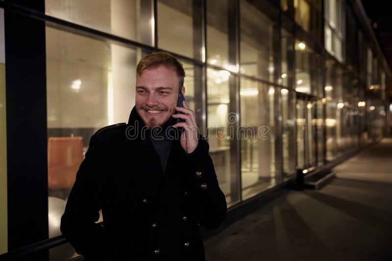 Night time, one young smiling and happy man, 20-29 years, talking over his phone, standing in Autumn coat on street, in front of stock image