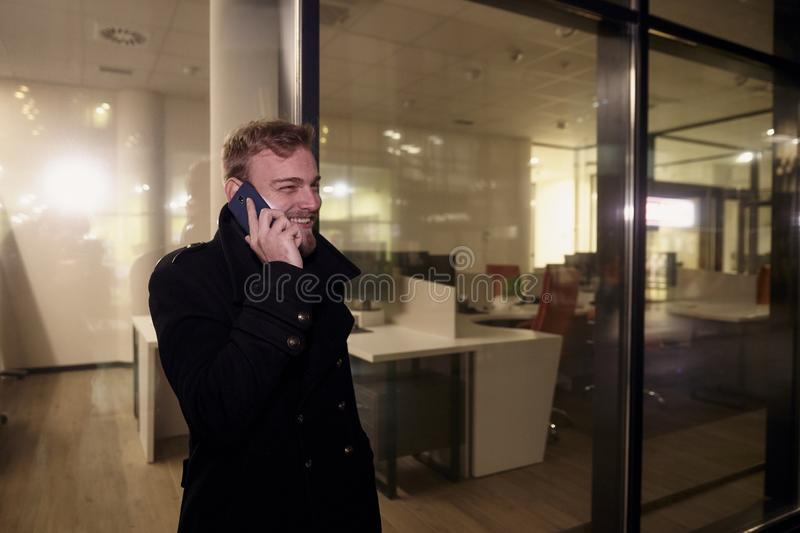 Night time, one young smiling and happy man, 20-29 years, talking over his phone, standing in Autumn coat on street, in front of stock photos