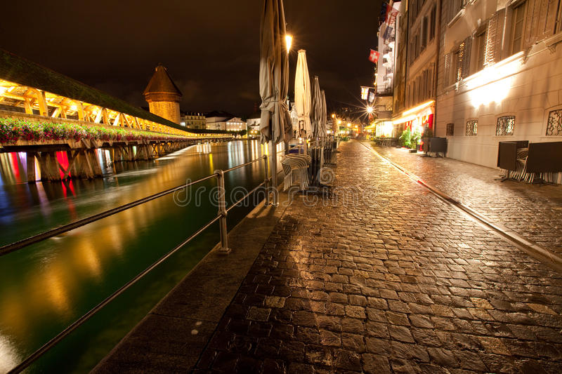 Night time scene of Lucerne along river. Night time scene of Lucerne water front along the Reuss river with view of the Kapell bridge royalty free stock photos