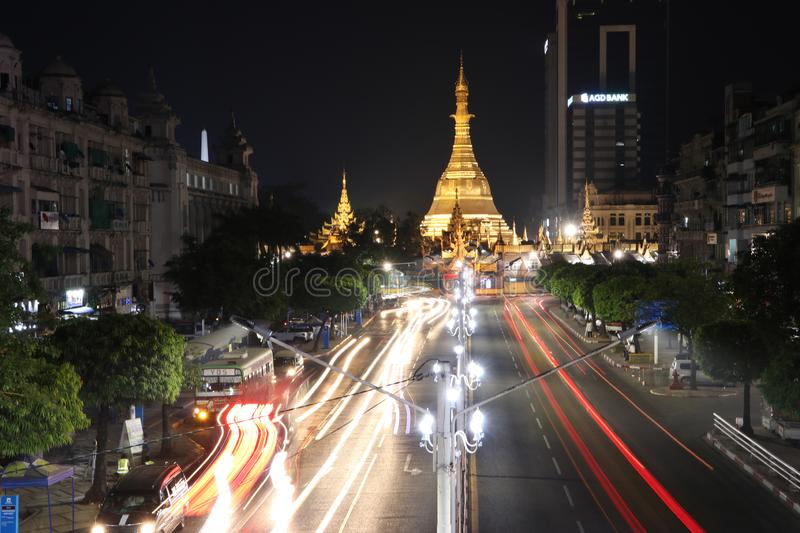 Night time and speed of light at golden octagon of Sula pagoda located in the heart of downtown Yangon with building and many cars. Yangon, Myanmar Feb 21, 2019 stock image