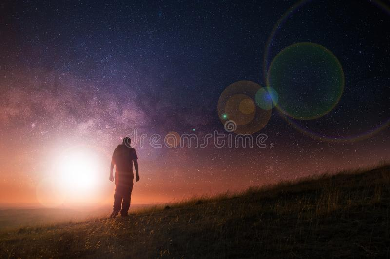 A night time stars edit of a silhouette of a lone man with a rucksack walking towards a light in the nights sky on a hill.  stock photos