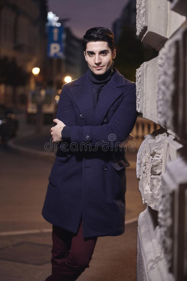 Night time sunset, one young man, 20-29 years old, leaning on wall on street building, looking to camera. wearing Autumn clothes stock photos