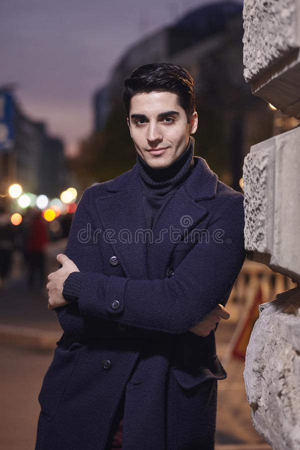 Night time sunset, one young man, 20-29 years old, leaning on wall on street building, looking to camera. wearing Autumn clothes royalty free stock photography