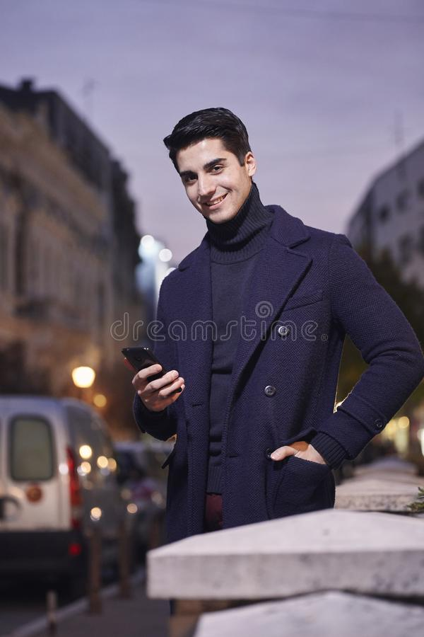 Night time sunset, one young man, 20-29 years old, standing, looking to camera. holding smartphone, wearing Autumn clothes royalty free stock photography