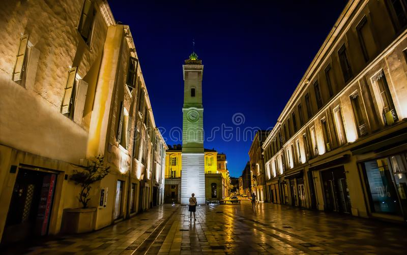 Night time view of clock tower, in center shopping center, Nimes France royalty free stock images