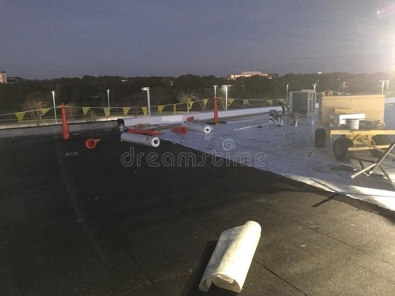 Night time view of the removal of Modified Cap sheet Commercial flat roof conversion to TPO with safety flags. Cones, materials, tools and gang box stock photo