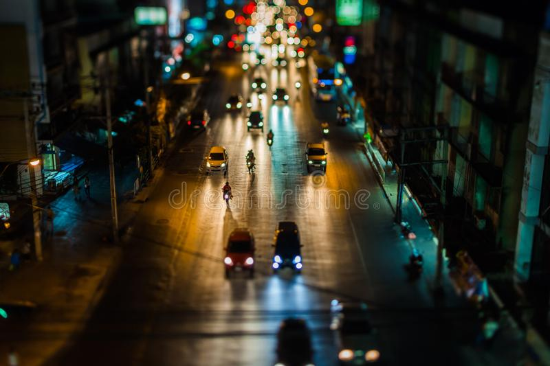 Night traffic in Bangkok. Street in the city center filled with cars passenger buses bikes and taxis. Night city lights up. Car headlights are reflected from stock image