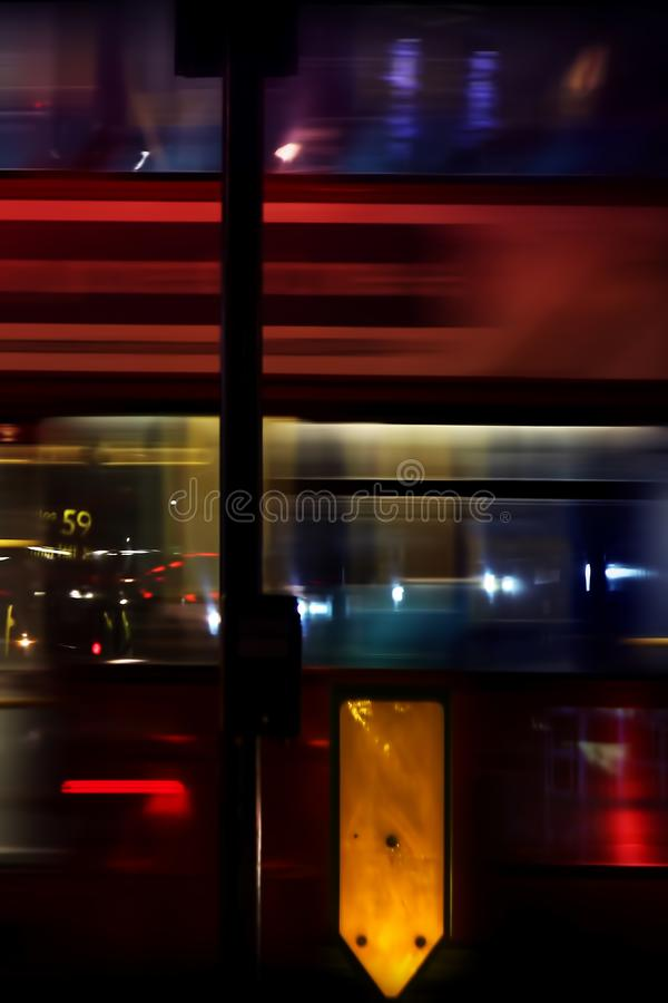 Night traffic in the city. A blurred fast moving bus with colorful lights and traffic signs