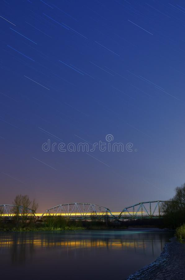 Night train on the bridge. Under the sky full of stars watched on a winter night stock image