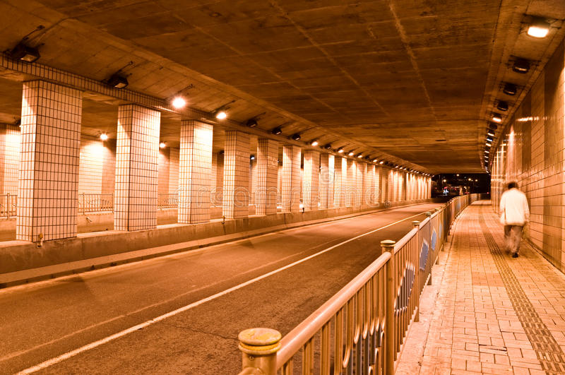 Night Tunnel. A lone man walks through a brightly lit tunnel at night stock photography