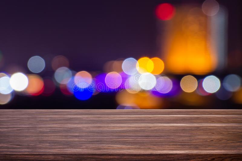 Night twilight blurred light bokeh in downtown bangkok empty of dark wood table abstract background for montage product display stock images