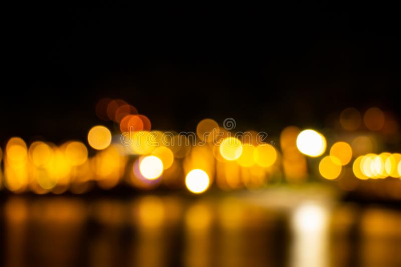 Night twilight blurred light gold bokeh reflecting on the sea surface water abstract background stock photos