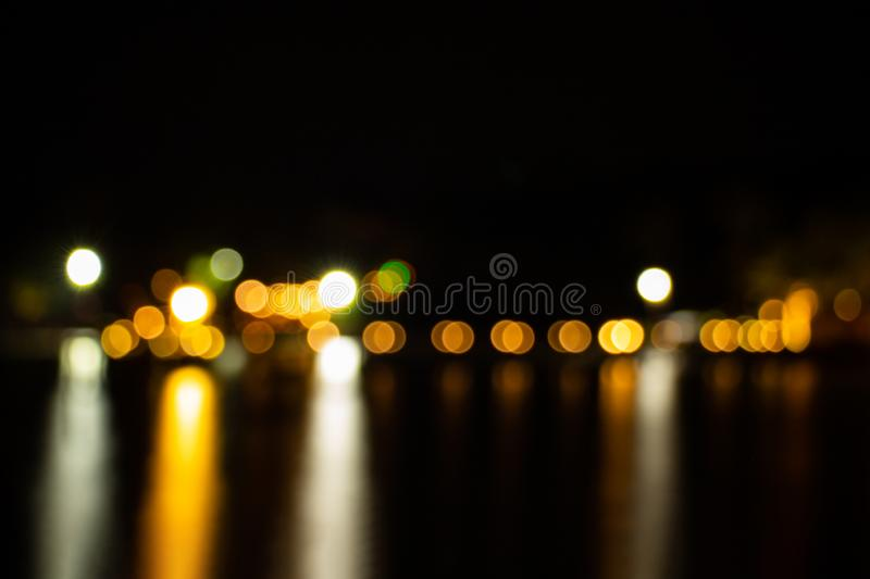 Night twilight blurred light gold bokeh reflecting on the sea surface water abstract background stock photo