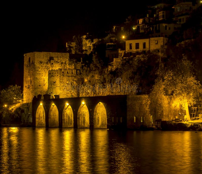 Night view of ancient stone ship port, castle, walls with lights reflected to the sea and behind it old city houses Alanya Antalya royalty free stock photography