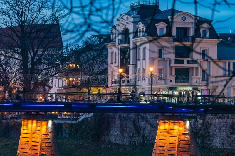Night view of the bridge with pedestrians in the old part of the city. UZHGOROD. stock image