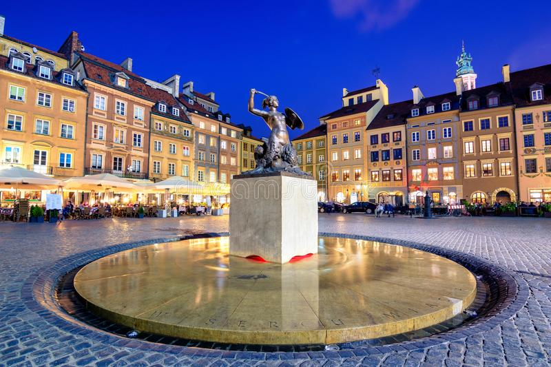 Night view of the bronze statue of Mermaid on the Old Town Market Square of Warsaw, surrounded by colorful old houses. Night view of the bronze statue of stock photos