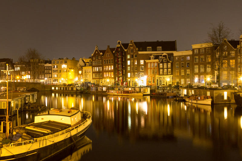 Night view of buildings in Amsterdam reflected in a canal, Holl stock image