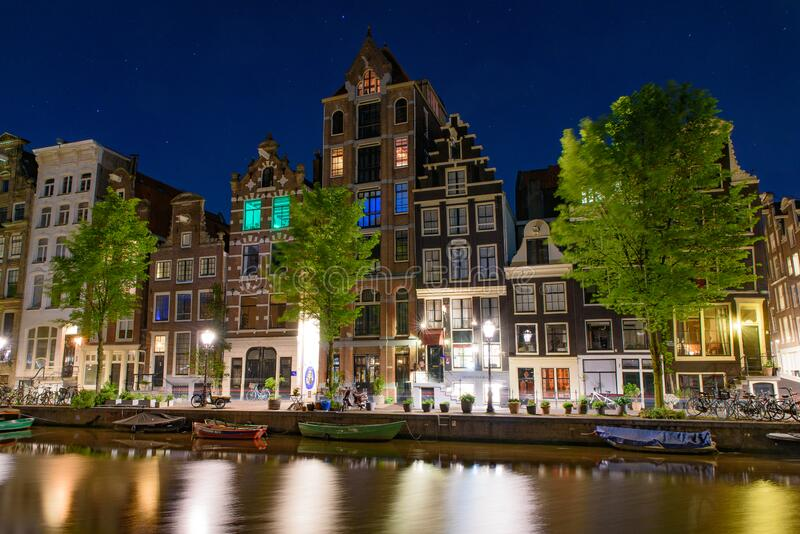Night view of buildings and boats along the canal in Amsterdam, Netherlands royalty free stock photo