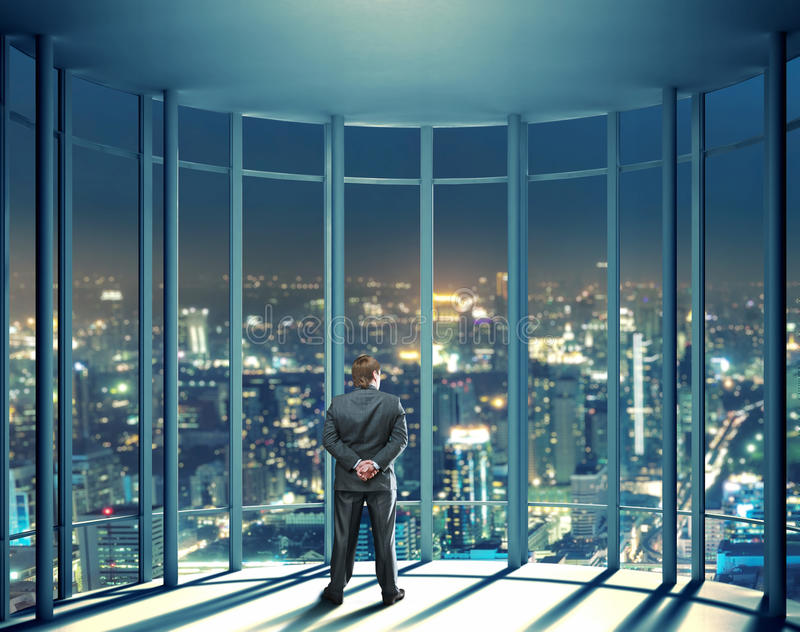 Night View Of Buildings And Man From Glass Window Stock