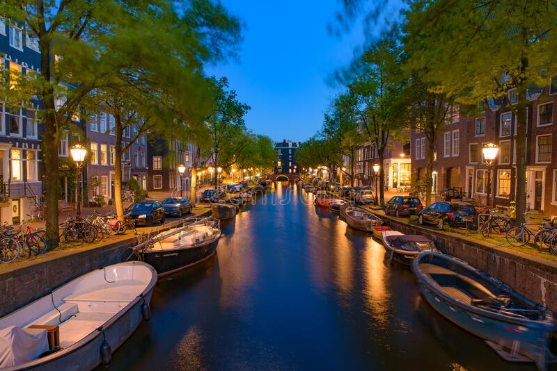 Night view of buildings and boats along the canal in Amsterdam, Netherlands royalty free stock photography