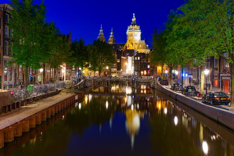 Night view of buildings and boats along the canal in Amsterdam, Netherlands royalty free stock images