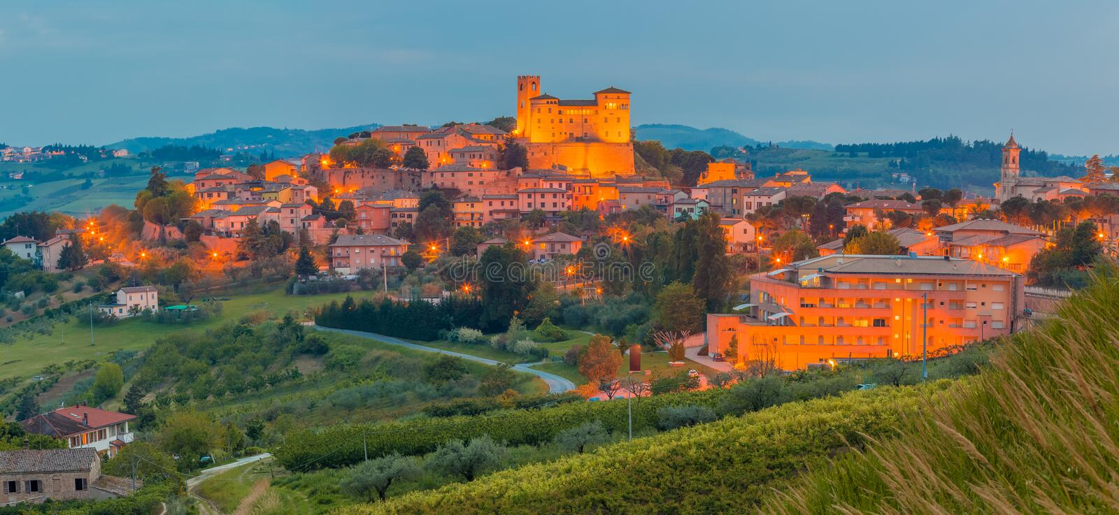 Night view of castle and roofs. Of houses in the tranquility of a medieval village in the hills of Romagna in Italy royalty free stock images