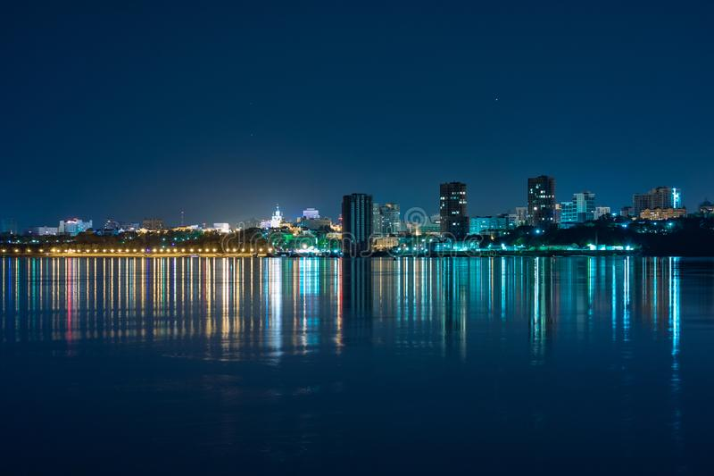 Night View of the city of Khabarovsk from the Amur river. Blue night sky. The night city is brightly lit with lanterns. Night View of the city of Khabarovsk stock image