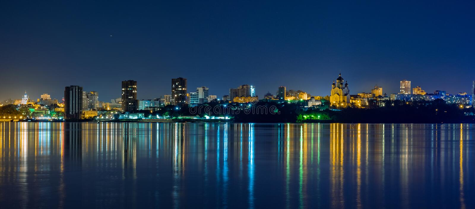 Night View of the city of Khabarovsk from the Amur river. Blue night sky. The night city is brightly lit with lanterns. Night View of the city of Khabarovsk stock photo