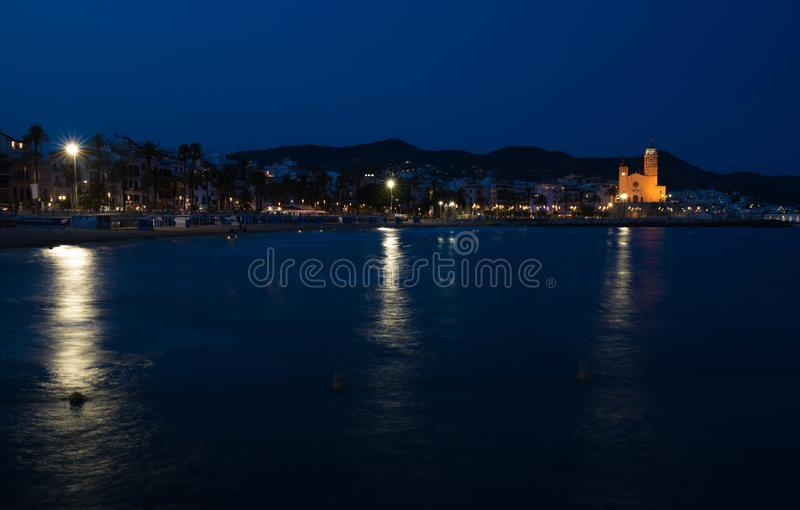 Night view of the coast in Sitges town near Barcelona in Catalonia,Spain with Parroquia de Sant Bartomeu i Santa Tecla church royalty free stock photography