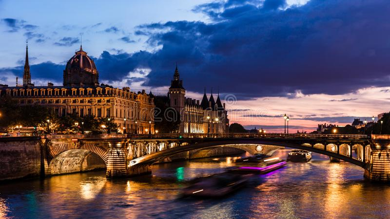 Night view of Conciergerie Castle and Pont Notre-Dame bridge over river Seine. Paris, France stock photography