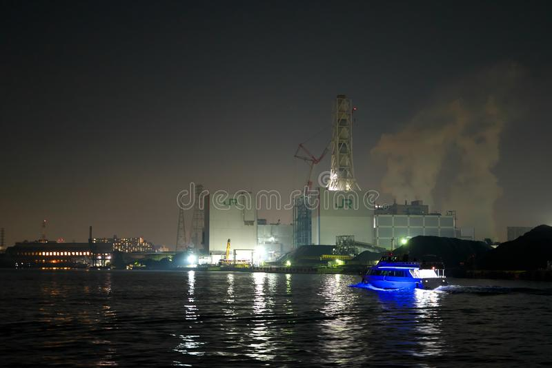 Night view of heat power plants viewed from a boat in Kawasaki just after the sunset royalty free stock photos