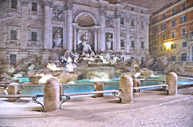 Night view with heavy snowfall on Trevi Fountain square, the largest Baroque fountain in the city and one of the most famous foun stock photo