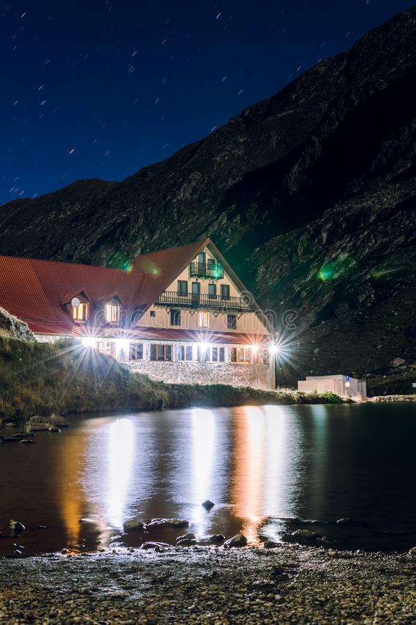 Night view on house, hotel on the shore of a mountain lake, Balea Lac, tourism and vacation concept, travel and active lifestyle,. Vertical photo royalty free stock image