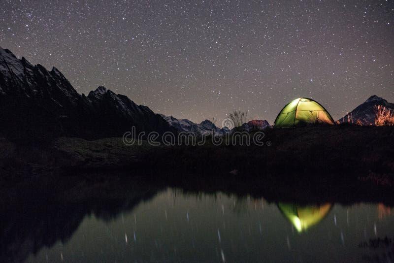 Night view of illuminated tent near lake stock photo