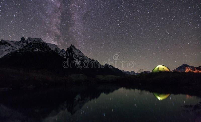Night view of illuminated tent near lake stock images