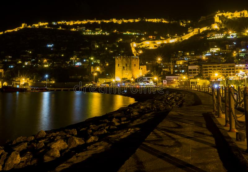 Night view image of old city near sea with ancient castle, houses and stone walls scenery between lights from Alanya Antalya Turke. Y travel royalty free stock photos