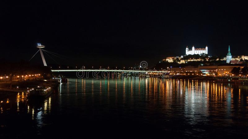 Night view of the lighted SNP bridge over Danube river and castle. Bratislava, Slovakia. Night view of the lighted SNP bridge over Danube river and castle in stock photography