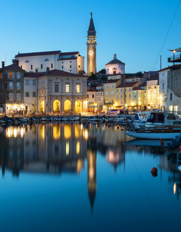 Night view of old city Piran in Slovenia. Beautiful cityscape through marina to Tartini Square stock photos
