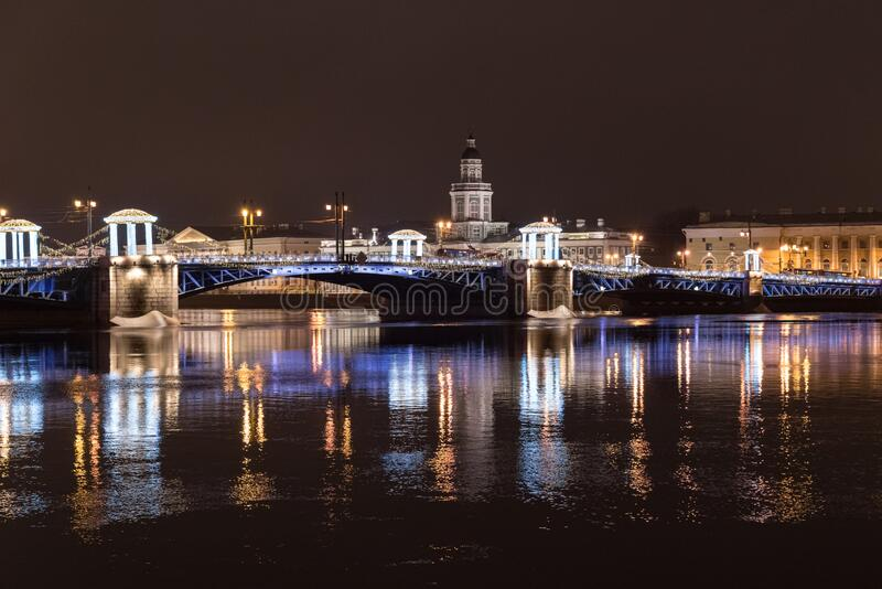 Night view of the Palace Bridge decorated with festive lights for the New Year. Sankt-Peterburg, Russia.  stock photos