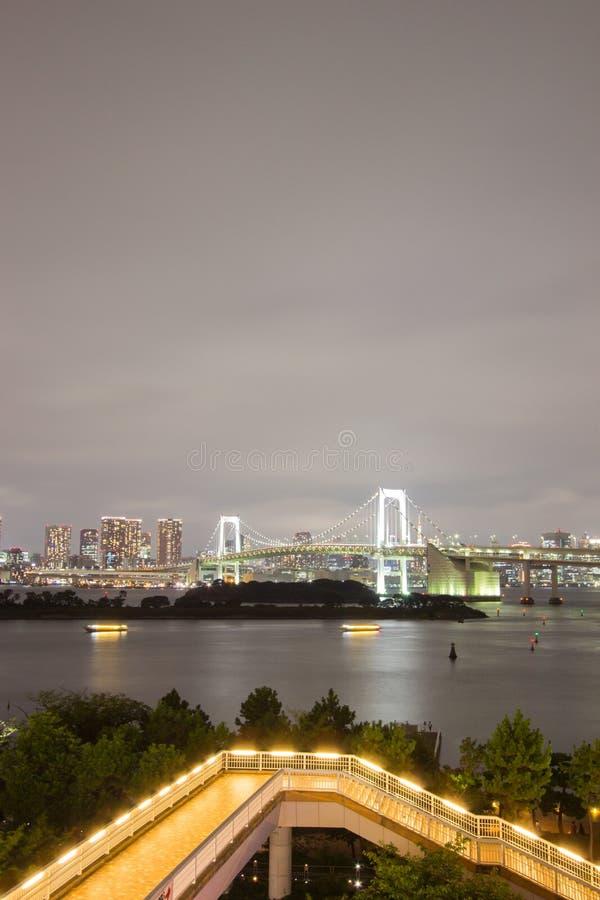 Night view of Rainbow Bridge and the surrounding Tokyo Bay area as seen from Odaiba,Minato, Tokyo, Japan. Rainbow Bridge is a suspension bridge crossing royalty free stock photo