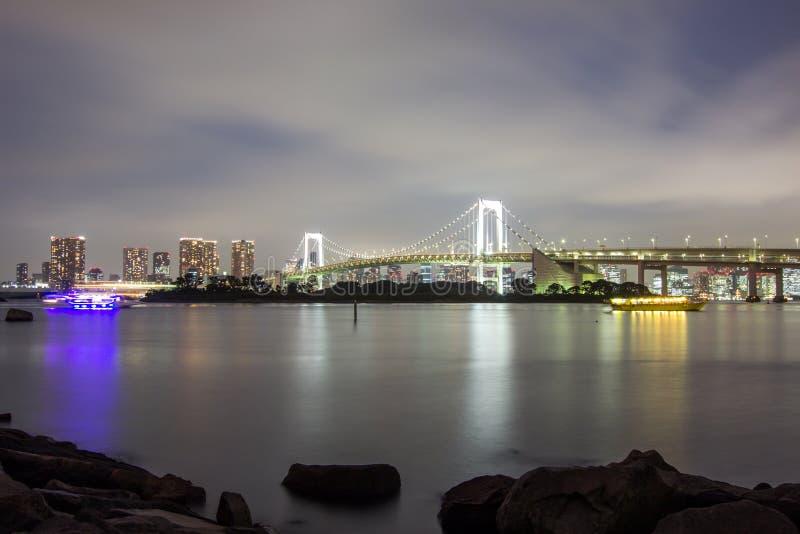 Night view of Rainbow Bridge and the surrounding Tokyo Bay area as seen from Odaiba,Minato, Tokyo, Japan. Rainbow Bridge is a suspension bridge crossing stock photo