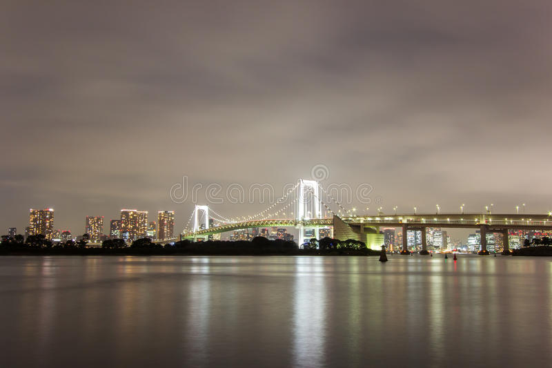 Night view of Rainbow Bridge and the surrounding Tokyo Bay area as seen from Odaiba,Minato, Tokyo, Japan. Rainbow Bridge is a suspension bridge crossing royalty free stock photos